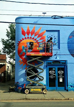 Nakima works on a piece of her mural at Solstice Tavern.