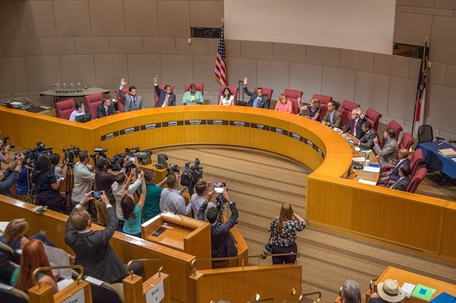 Council members raise their hands in approval of bringing the RNC to Charlotte. (Photo by Grant Baldwin)