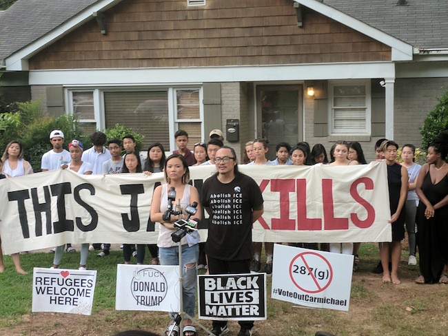 Cat Bao Le (left) and Tin Nguyen stand with community support outside of their home. (Photo by Ryan Pitkin)