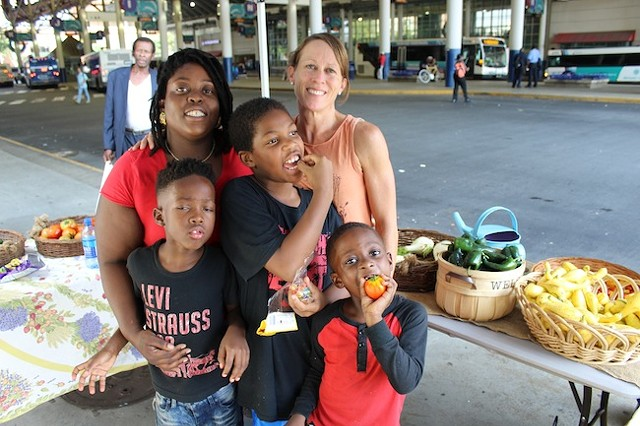 Caroline Miller (right) with Trenisha Birtha and her sons at the Transit Center market that they run for The Bulb on Thursdays. (Photo by Ryan Pitkin)