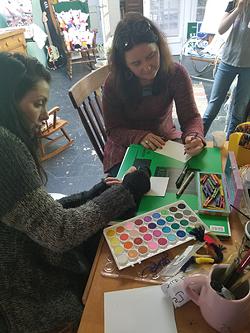 Lauren Kestner (left) and Hillary Belk collage together at a past workshop.