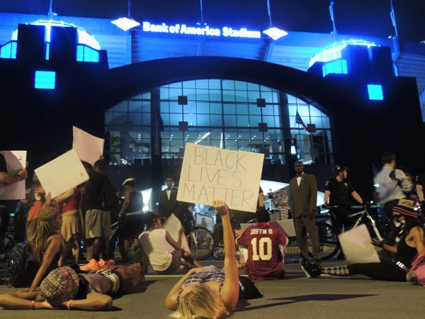 Protesters lie, sit and stand on Stonewall Street where fans were streaming out of a Panthers preseason game on Saturday, August 22.