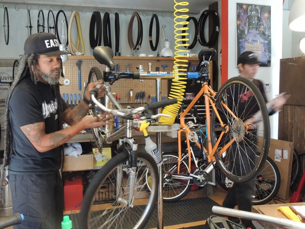 Dread (left) and Cory work on bikes at The Spoke Easy. The orange bike had been hit by a car the previous day. (Photo by Ryan Pitkin)