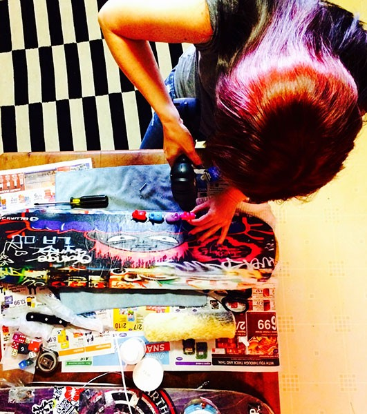 Phoebe Alicia constructing her art, which is wheat-pasted on skateboards. (Photo by Phoebe Alicia)