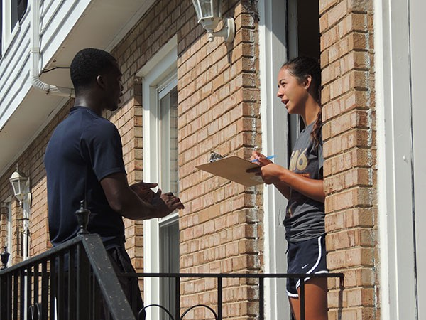 Diaby speaks with a woman while canvassing in east Charlotte.  (Photo by Ryan Pitkin)