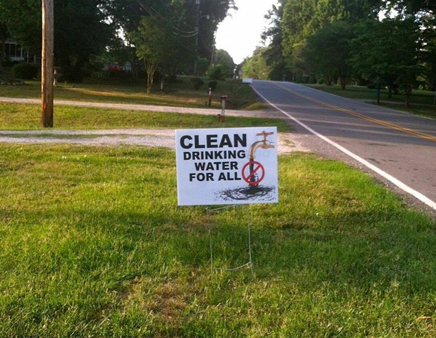 A yard sign in Gaston County near the Allen Steam Station calls for clean tap water. Many in the area are still living off bottled water provided by Duke Energy, as they have for about a year and a half now. - PHOTO COURTESY OF AMY BROWN