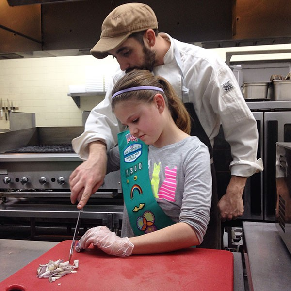 Chef Clark Barlowe shows a Girl Scout how to approach the chopping block. (Courtesy of Clark Barlowe)