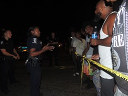 Residents argue with officers blocking off the crime scene early on Tuesday night. - RYAN PITKIN