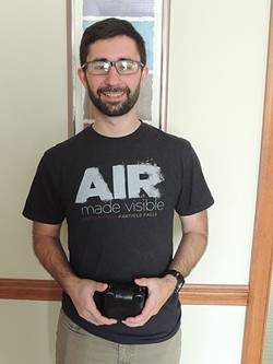 Calvin Cupini holds an AirBeam, used to measure air quality at different points around the city. - RYAN PITKIN