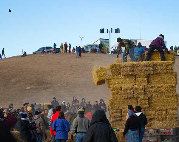 Water protectors in the Oceti Sakowin camp prepare hay that will be used for insulation during the coming winter. - GARRETT AMMESMAKI