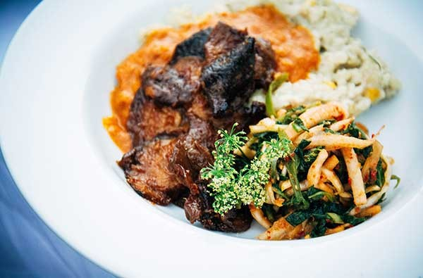 Coconut and fresh corn risotto, peach BBQ oyster mushrooms and kimchi slaw from Nourish Charlotte. - JAKE YOUNT