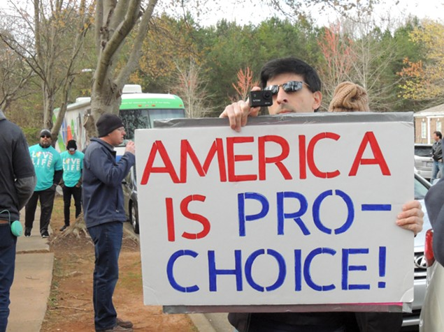 A counter-protester aims a sign and a camera at a group of protesters (behind the camera). Daniel Parks, leader of extreme anti-abortion group Cities4Life, stands behind him speaking into a microphone hooked to a large speaker aimed at the clinic.