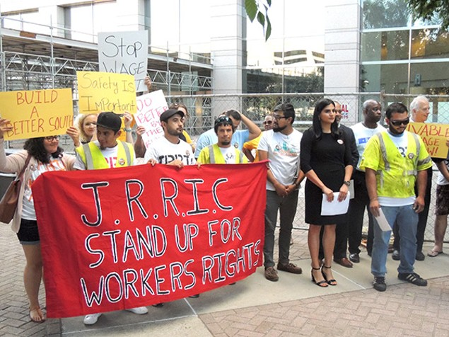 Supporters of the Justice and Respect in the Reinforcing Industry Coalition stand outside the Charlotte-Mecklenburg Government Center. To the right, in yellow, Alexis Gonzalez prepares to address media. (Photo by Ryan Pitkin)