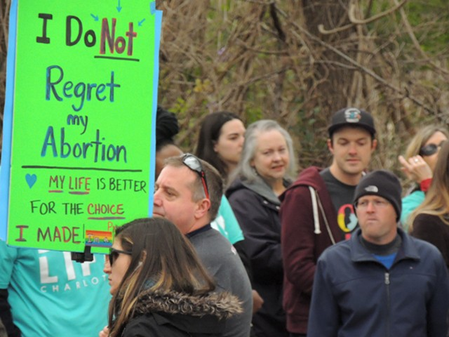 A pro-choice counter-protester stands between a large group of prayer marchers and A Preferred Women's Health Center in March. (Photo by Ryan Pitkin)