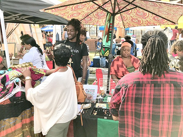 Ali Steele (in black T-shirt) sells his designs at the Oct. 21 Bla/Alt Music Festival at Camp North End. (Photo by Mark Kemp)