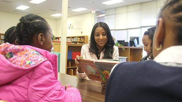 Nikki Davis reading books with kids at local schools, where she often visits. (Photo courtesy of I'Merge)