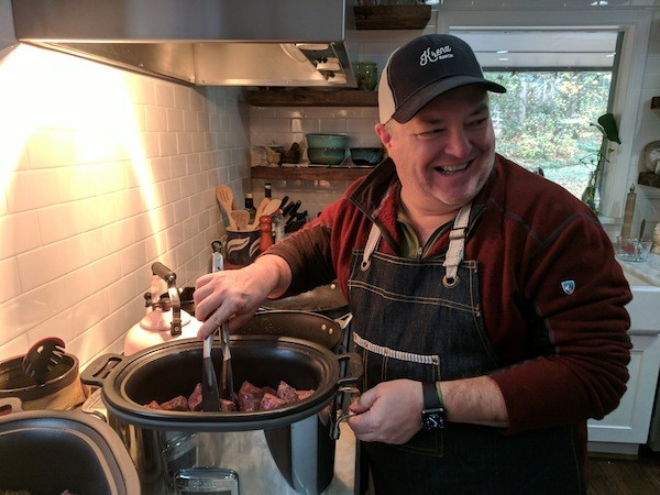 Peter Taylor at his south Charlotte home, preparing braised short ribs in a slow cooker. (Photo by Ryan Pitkin)