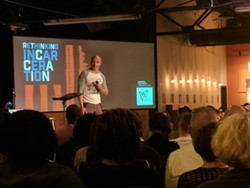 Toussaint Romain addresses a crowd of around 200 people at Warehouse 242 on Tuesday.