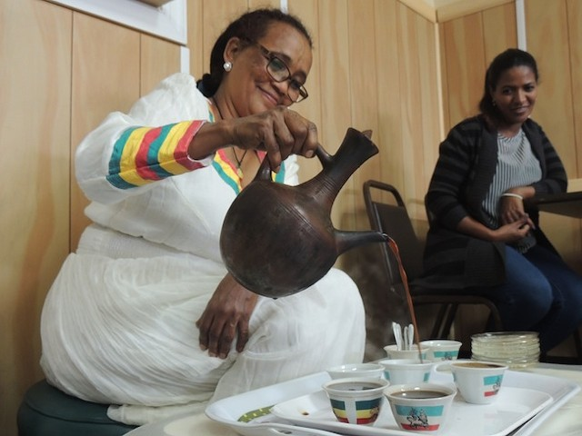 Meshasha carries out an Ethiopian coffee ceremony.
