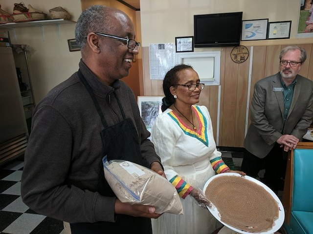 Zerabruk Abay (left) and his wife Tsige Meshasha explain how they make injera. In the background, Munching Tour guide Tom Hanchett looks on. (All photos by Ryan Pitkin)