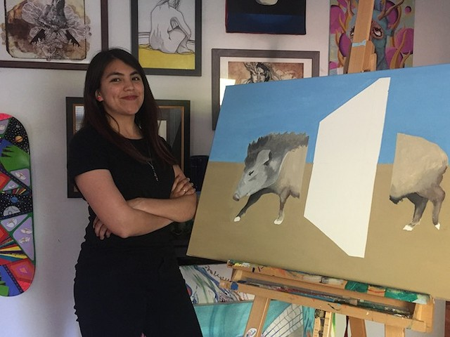 """Megan Walsh with her painting """"I Resist Manmade Borders"""""""