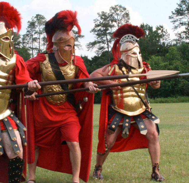 Participants dressed in Greek soldier uniforms pose in a defensive stance with spears. (Photo Courtesy of Yiasou Greek Festival)
