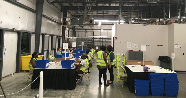 Durham County Board of Elections staff process absentee ballots in October 2020 at the agency's warehouse. Each blue bin holds ballots from a different precinct. The workers are removing ballots from absentee-by-mail envelopes and flatten them, to be scanned in batches later on. Jordan Wilkie / Carolina Public Press