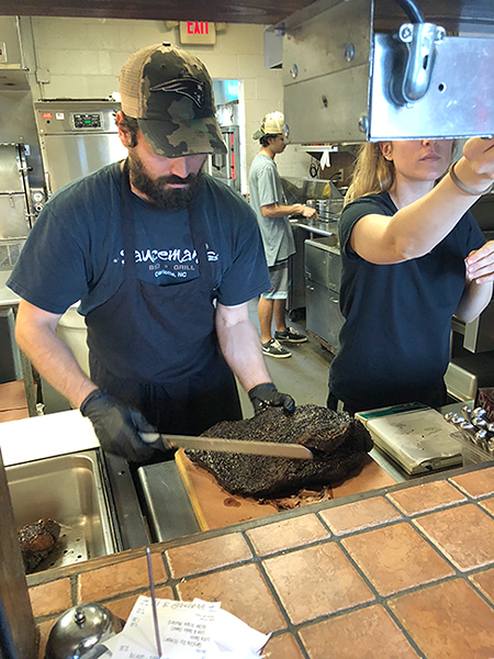 An employee begins to slice off pieces from a brisket. (Photo by Sophie Whisnant)