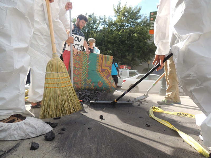 Protesters sweep coal under Gov. McCrory's rug outside of the Westin on Thursday afternoon. - RYAN PITKIN