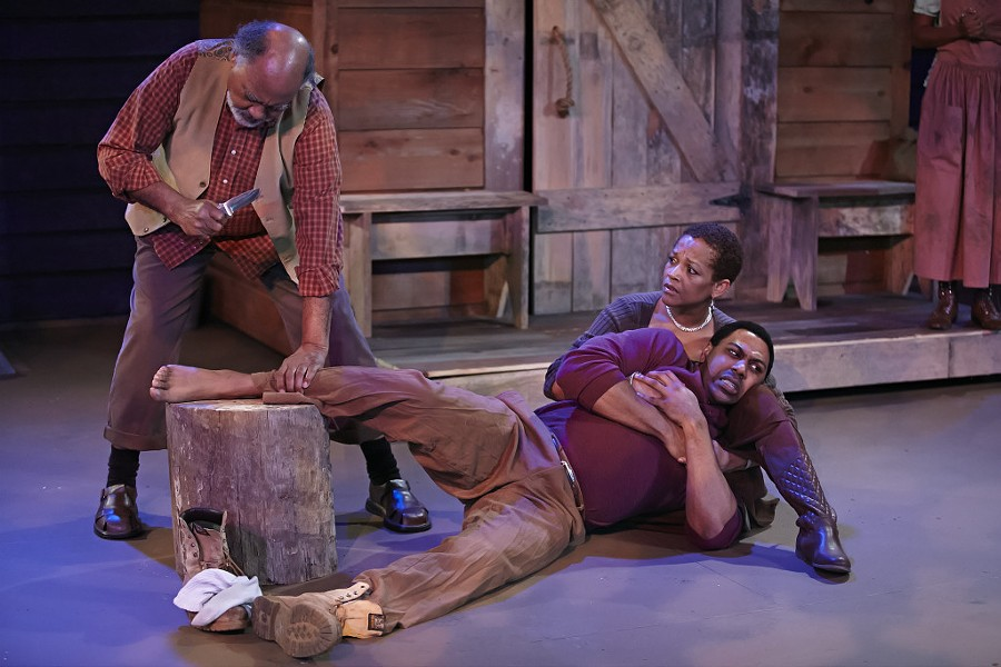 Jones, as Penny, cradles Jonavan Adams, as Hero, in 'Father Comes Home from the Wars.' John Price, at left, plays the Oldest Old Man. (George Hendricks Photography)