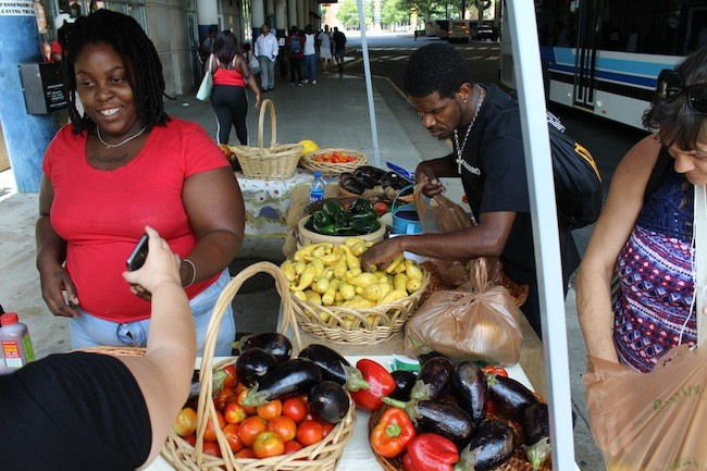 Trenisha Birtha (left) chats with customers at a recent Bulb market while Stephen Hayes picks out ingredients for a lasagna he planned on making. (Photo by Ryan Pitkin)