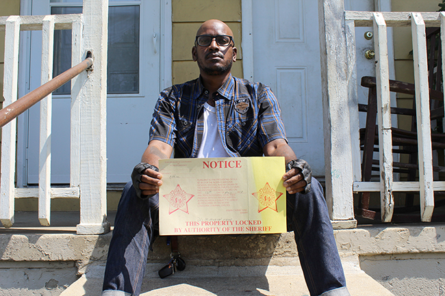 Jacobs holds an eviction notice placed in the door of a Brookhill Village home in May. (Photo by Ryan Pitkin)