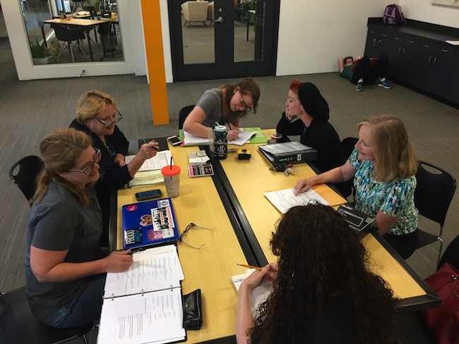 The production team at work [left to right]: Susan Hatem, Anne Lambert, Brenna Skinnon, Ramsey Lyric, Jackie Hohenstein and Barbara Berry [back to camera]. (photo courtesy of Charlotte's Off Broadway)