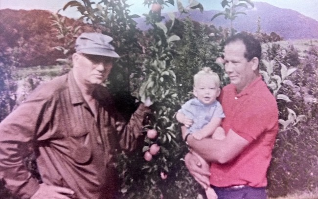 From left: Perry Lowe Sr. and Perry Lowe Jr. holding Perry Lowe, III. (Photo Courtesy of Perry Lowe Orchards)