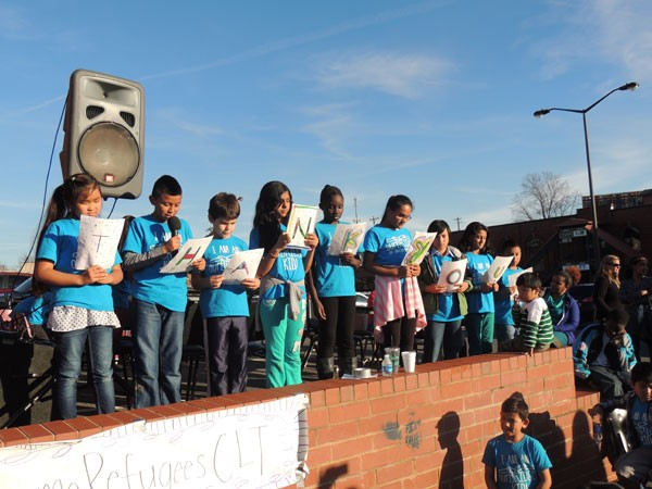 Refugee and immigrant children thank ourBRIDGE for their service with handmade signs and by reciting a poem. (Photo by Ryan Pitkin)