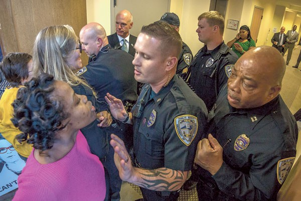UNC Charlotte student Ashley Williams (pink shirt) and other protesters confront campus police during an attempt to enter the board meeting. (Photo by Grant Baldwin)