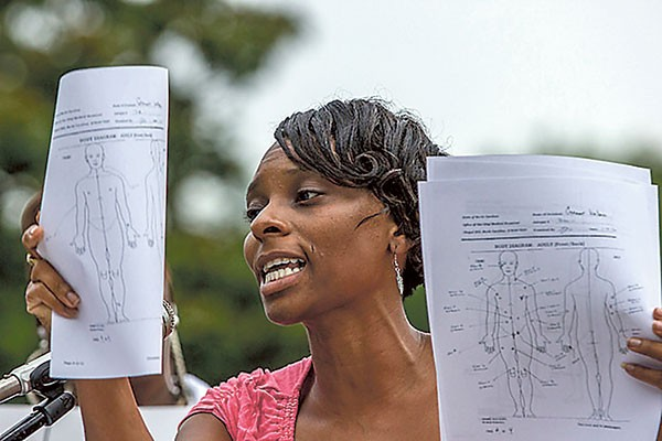 Demika Wallace, cousin of Germonta Wallace, who was killed by CMPD officers in January, holds autopsy diagrams of his 26 bullet wounds as she speaks at an event at Marshall Park on July 11.