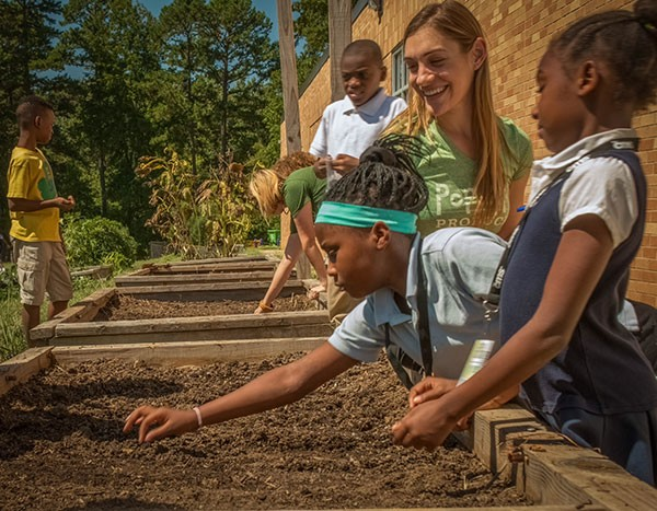 Amanda Zullo (in green) works with students at Shamrock Gardens Elementary School. - ALEX WALKER