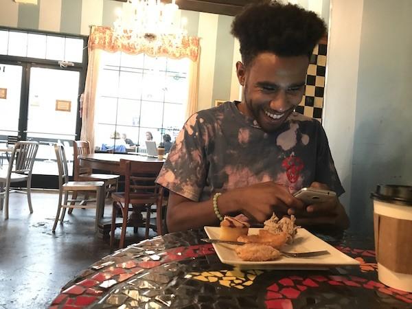 Hood picks at pastries and checks his texts at Amelie's. (Photo by Mark Kemp)