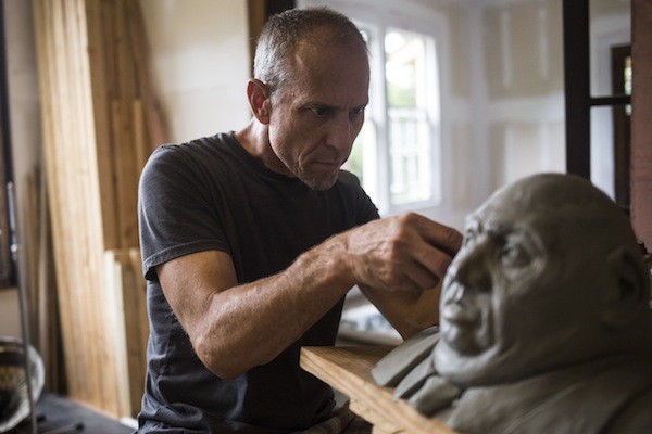 ArtPop alum Nicholas Sorlien works on one of his concrete heads. (Photo by Katie McLean)
