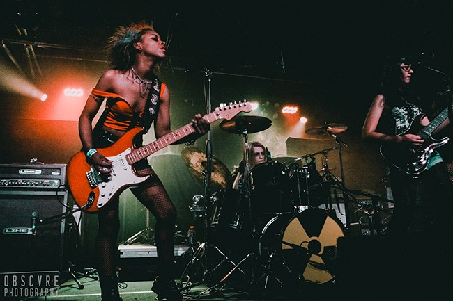 Brunache (left) rocks her Strat with Death of August; her longtime band mate Helena Radeva is at far right. (Obscvre Photography)