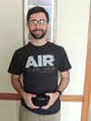 Calvin Cupini holds an AirBeam, used to measure air quality at different points around the city.