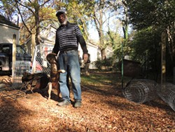 David Boulware with this dog, Miracle. Miracle was the 20th recipient of a fence through Humane Society of Charlotte's I-Build program in Enderly Park since July 2014. (Photo by Ryan Pitkin)