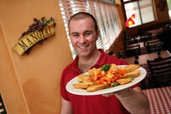 CATALINA KULCZAR - UNCOMPLICATED AND FINE: Owner Lando Vicidomini with the calamari appetizer