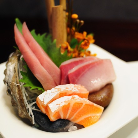 A floral arrangement of premium sushi: buttery salmon, yellowtail, and tuna