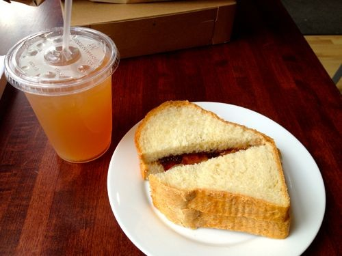 An almond butter and strawberry-vanilla jam sandwich with peach lemonade