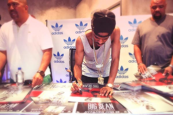 Big Sean signs posters in a Los Angeles Adidas store on June 24