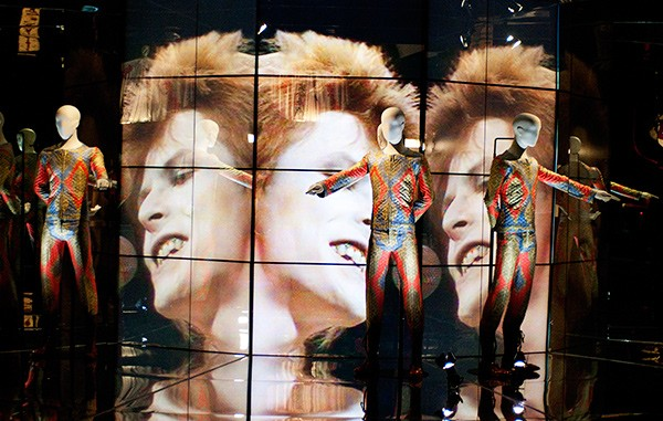 "Bowie's Top of the Pops performance plays on a loop behind his quilted ""Starman"" suit."