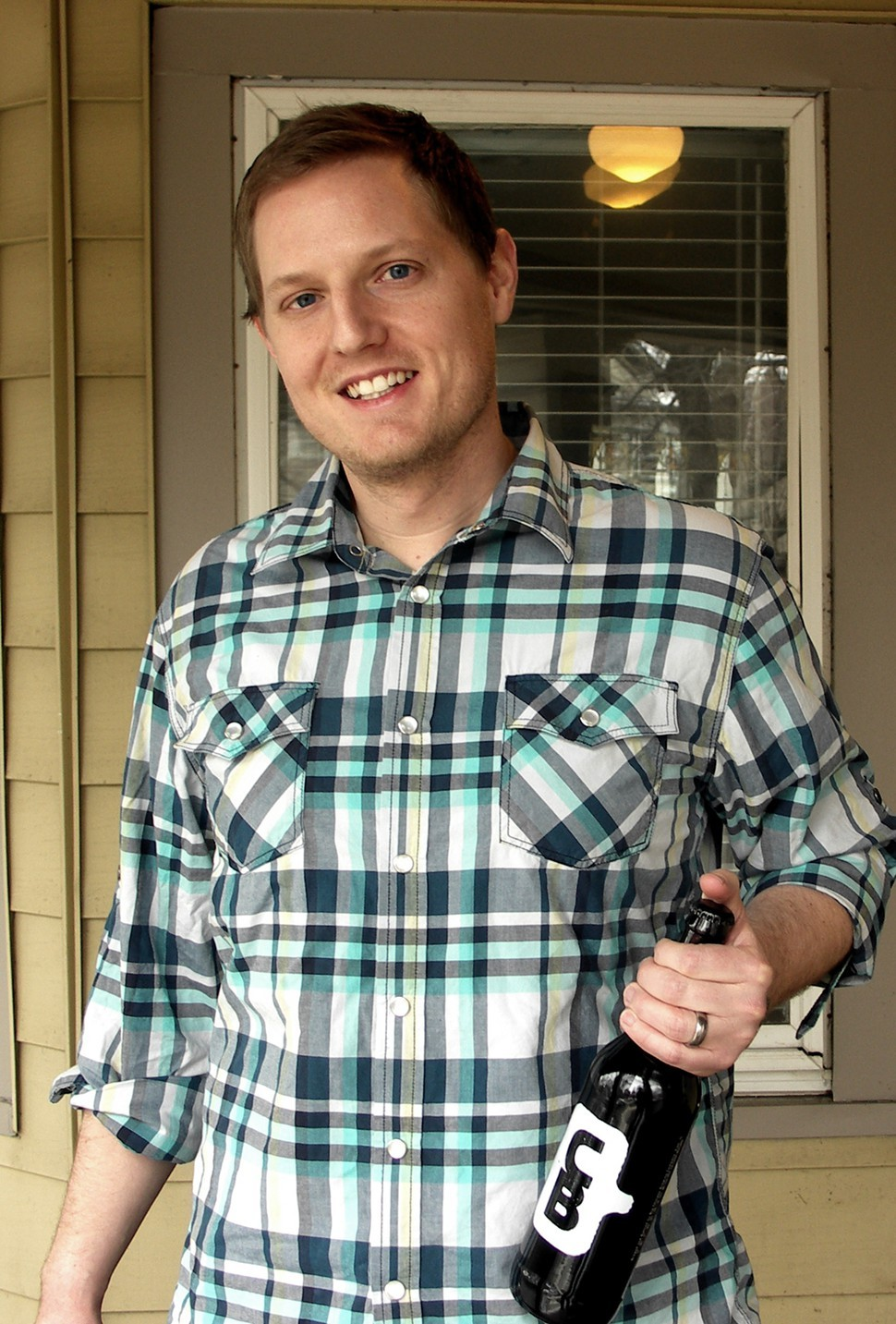Cahoots founder Dustin Adkison takes a bottle out to his porch for some fresh air.