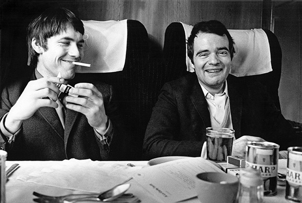 Chris Stamp and Kit Lambert travel by train to Manchester with the Who in 1966.